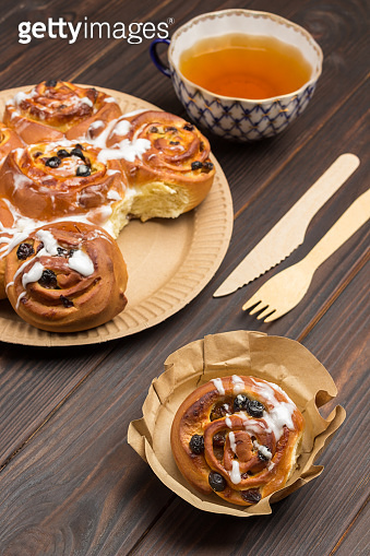 Baked buns with raisins in cardboard disposable plate.