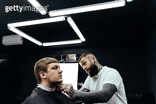 Tattooed Barber trimming bearded man with shaving machine in barbershop. Hairstyling process. Hairstylist cutting the beard of a bearded male