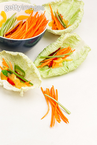 Sliced carrots. Vegan cabbage leaf snack with carrots.