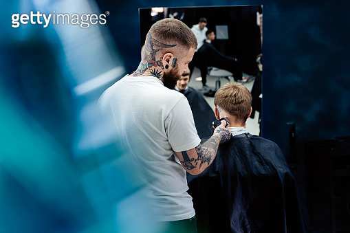 Male haircut with electric razor. Tattooed Barber makes haircut for client at the barber shop by using hairclipper. Man hairdressing with electric shaver