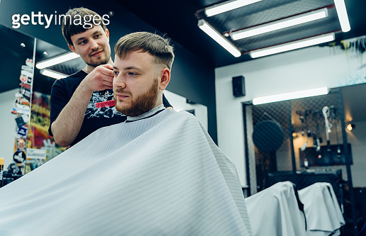 Male haircut with electric razor. Barber makes haircut for client at the barber shop by using hairclipper. Man hairdressing with electric shaver