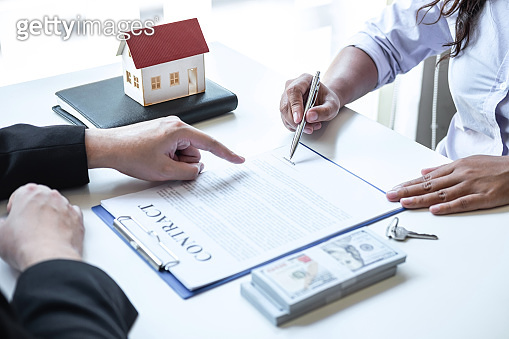 Estate agent broker pointing contract form to client signing agreement contract real estate with approved mortgage application form, buying or concerning mortgage loan offer for and house insurance