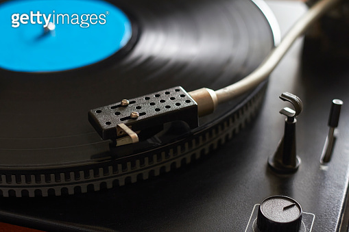 Close-up of blue music record on turntable, turntable needle playing music, selective focus