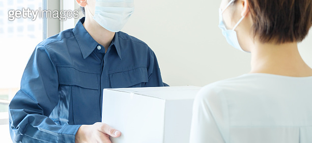 young asian courier delivering box