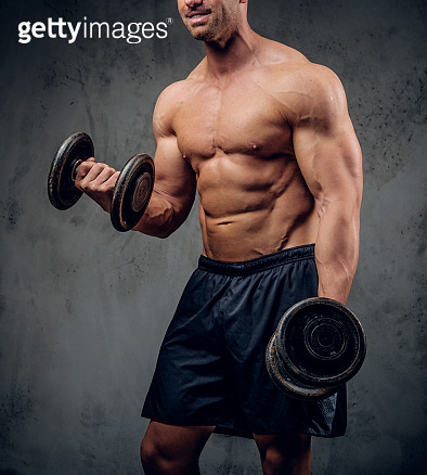 Strong male is doing exercises with barbells on the dark background