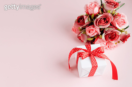 Gift box with bouquet of tred rose on pastel pink background. Spring or holiday concept, March 8, International Women's Day, birthday. Copy space, flat lay, Template mockup greeting card with place for text,