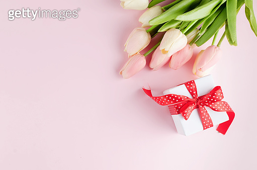 Gift box with bouquet of pink and white tulips on pastel pink background. Spring or holiday concept, March 8, International Women's Day, birthday. Copy space, flat lay, Template mockup greeting card with place for text,