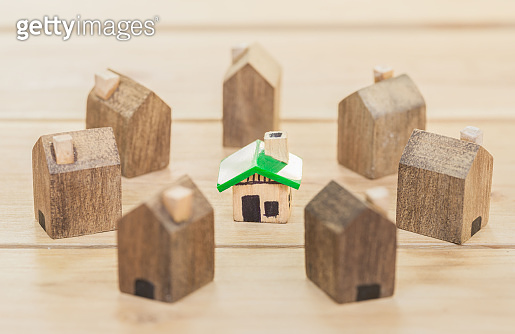 Green house in among wooden house for real estate. planning savings money of coins to buy a home concept for property