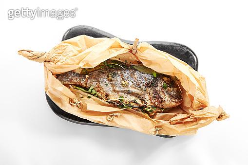 Baked dorado fish in parchment
