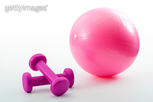 Strength increase through weightlifting and aerobic exercise  and muscle toning exercising concept inflatable fitness ball and pink weights isolated on white background