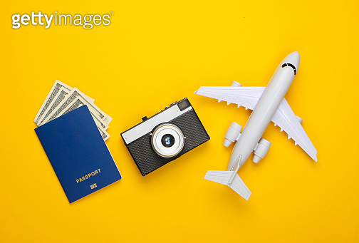 Travel flat lay composition. Plane figurine, camera, passport on a yellow background. Rest, vacation. Top view