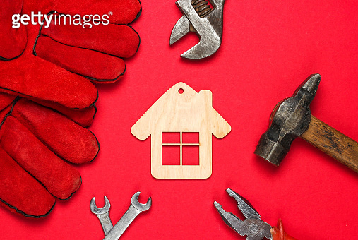 How to build a house? DIY working tools and mini house figurine on red background