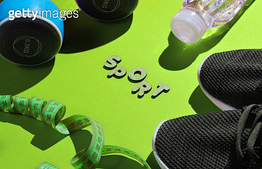 Healthy lifestyle. Dumbbells, ruler,  bottle of water, sneakers on green background with word sport. Slimming concept.