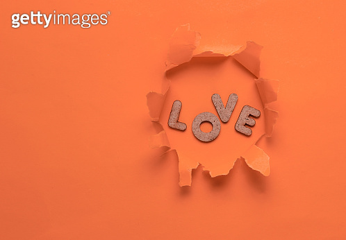 The word love in a torn hole of orange background. Top view