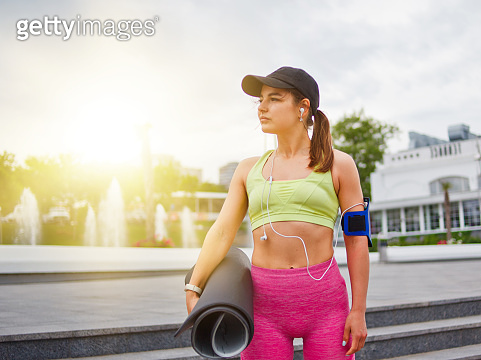 Athletic young woman in sportwear holds a yoga mat in her hand and listens to music with headphones outdoors