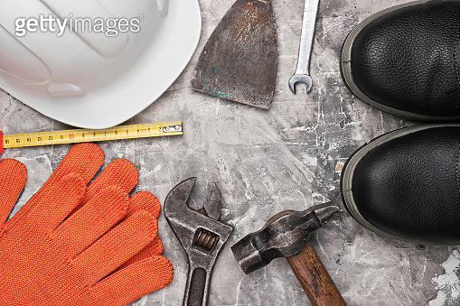 Safety equipment and work tool on gray concrete background. Top view. Copy space