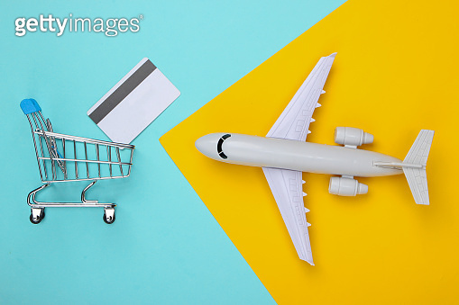 Air delivery and online shopping. Airplane and shopping trolley with a bank card on a blue-yellow pastel background. Flat lay cosposition. Top view