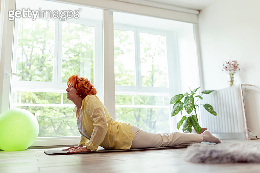 Active senior woman doing yoga session at home