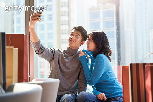 young asian couple taking a selfie in hotel room