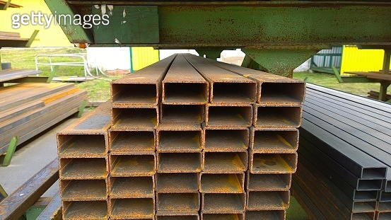 Rectangle Steel Tube in rows. Rectangular rusty pipe. Hot and cold rolled metal Tubing. Industrial metal supply. Warehouse and factory. Protection and prevent pipeline corrosion concept. Industry.