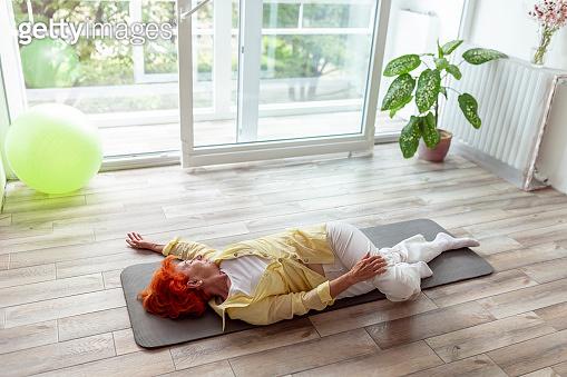 Senior woman doing spinal twist yoga exercise
