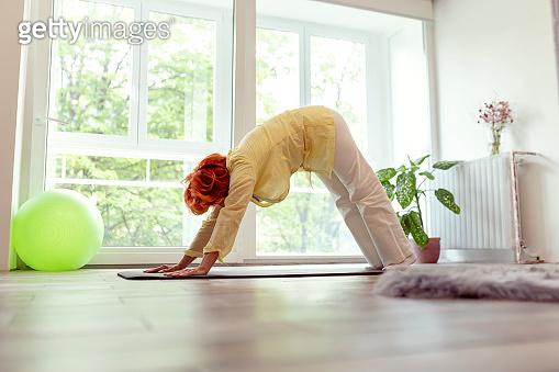 Senior woman holding downward facing dog yoga position