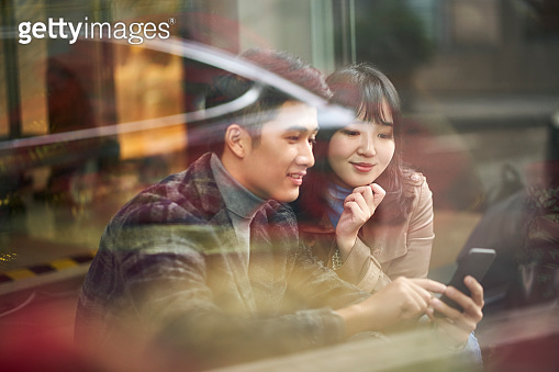 young asian couple looking at mobile phone together