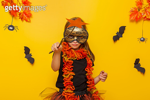 Little girl dressed as witch casting spells with magic wand for Halloween