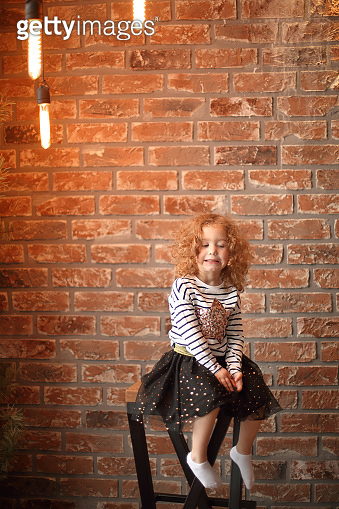 portrait of a little girl on a brick wall background.