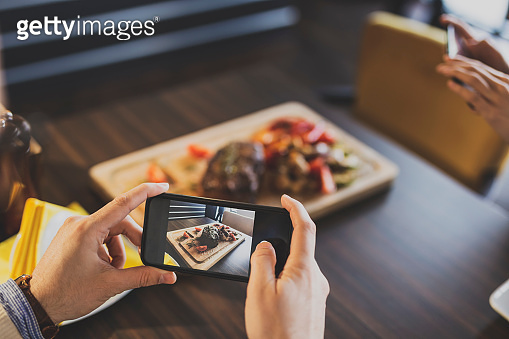 Couple photographing food in restaurant