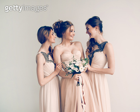 in full growth. girl bride with her friends in elegant dresses.