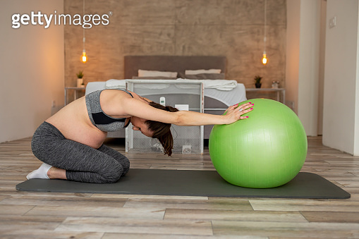 Pregnant woman working out with a fit ball