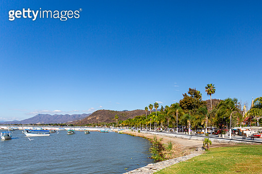 Boardwalk along the bay of Lake Chapala with motorboats on the calm waters, the pier and mountains