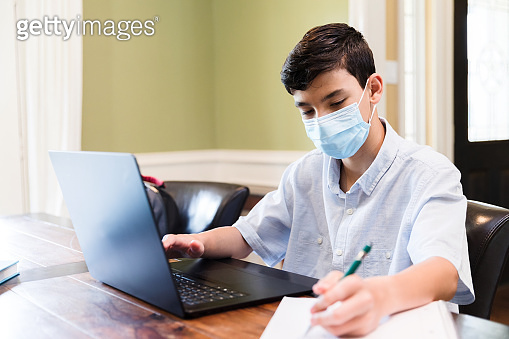 Teenage boy works on e-learning assignment while quarantined