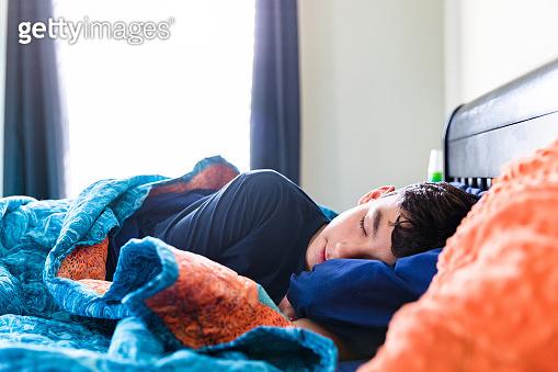 Sick male teenager sleeps comfortably