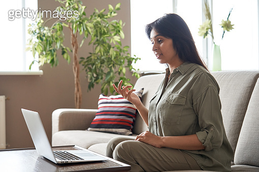 Young indian woman remote worker or distance teacher tutor speaking to webcam video conference calling on laptop computer sitting on sofa at home office. Virtual meeting online job interview call.