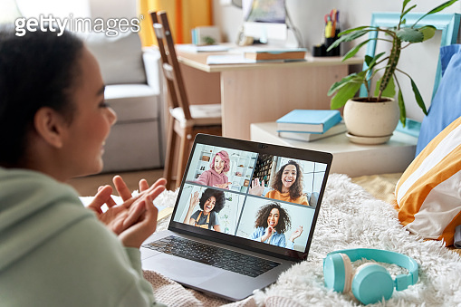 African teen girl talking with friends on distance video group conference call in bedroom. Mixed race teenager having fun chatting during virtual meeting at home communicating online lying in bed.