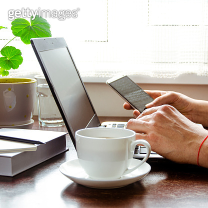 Businessman, freelancer holding pen, using mobile smart phone, working on laptop computer at home