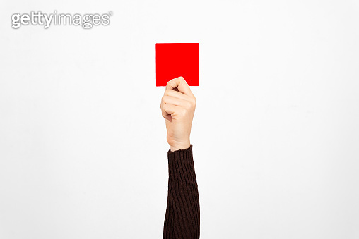 Hand of a business woman holding a red card in the air, white background. Fault concept.