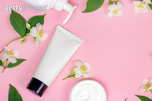 Top view of white plastic cosmetic container for moisturizing cream as a mock up with bright fresh jasmine flowers on light pink background with copy space. Body and skin care concept