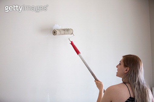 Young woman painting her wall with a paint roller and brush