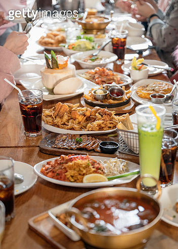 Various kind of gourmet food and drink with family eating on wooden table