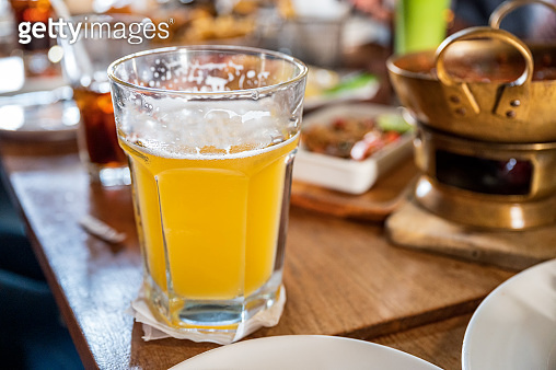 Craft beer with foam in big glass on wooden table in restaurant
