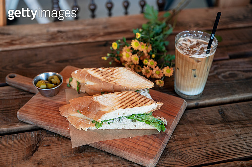 Chicken sandwich with iced coffee on wooden table