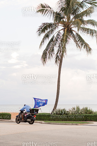 Man Driving a Scooter with a Large Blue Flag Waving in the Back on Palm Beach, Florida