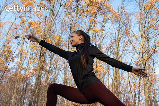 Young slim fit brunette girl in sportswear practicing asana yoga exercise among the autumn forest with yellow leaves, healthy life concept