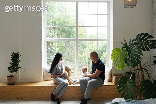 Young family, parents and little son sitting at the big window and showing a teddy bear to child