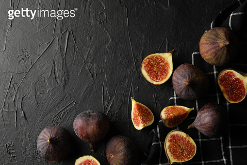 Towel and fig on black background, space for text