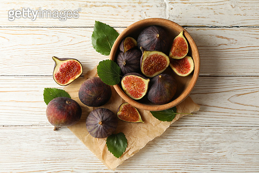 Bowl and baking paper with fig and leaves on white wooden background