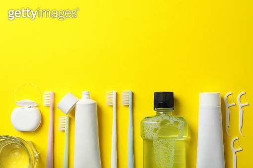 Tools for dental care on yellow background, space for text